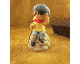 1978 Tiny Tim Bisque Holiday Collector Bell – Little Boy Sitting on Rocks Merri-Bell by Jasco – Vintage Christmas