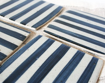 Set of four stoneware coasters with stripes in denim blue. Brush strokes, stenciled, graphic, linear, modern, bold.