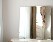 Beveled mirror with hanging mechanism and backing