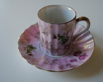 a vintage demitasse cup and saucer. made in japan with pink and green florals.