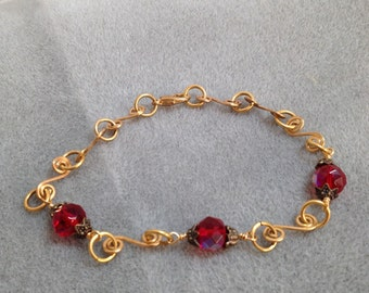 Red Czech glass and hand formed and hammered gold tone wire anklet