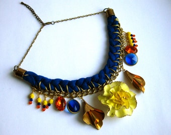 Braided necklace in blue t-shirt yarn, with yellow and orange beads and vintage pendants