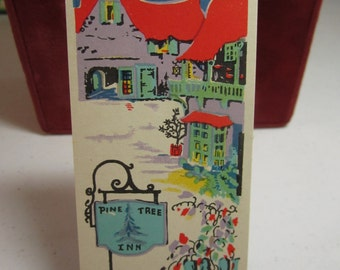 Colorful unused art deco 1930's christmas winter themed bridge tally red roofed cottages and sign reads Pine Tree Inn