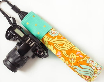 DSLR camera strap cover with lens cap pocket.  floral with gold x's.