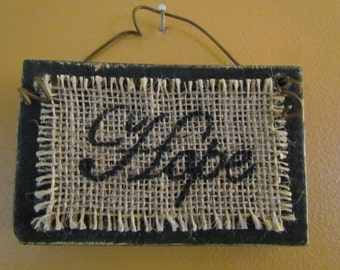 """Small, Distressed Wood Sign Painted Black With The Word """"Hope"""" Neatly Written in a Cursive Font in Black on Burlap with Rusty Wire Handle"""
