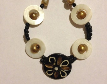 bracelet of gold pearls encircled by shell disks with handmade button