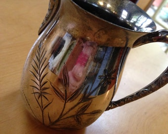 silver palte creamer with ethed floral patttern