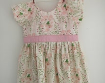 Frog princess dress with short sleeves in cream with a little green frog on lilypads with pink flower pattern and pink sash.