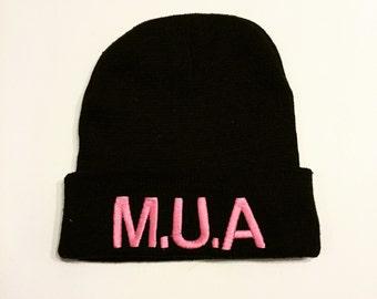 "black beanie with the phrase ""M.U.A"""