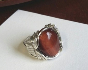 Beautiful Red Tigereye Cabochon stone set in a traditional Pharoah Ring wrap of sterlingt silver.  Size seven and one-half.