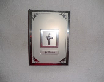 A new unused christening / baptism . Book photo album . With front window with crucifix inside . 18x 13 cm . 24 perspex pages .