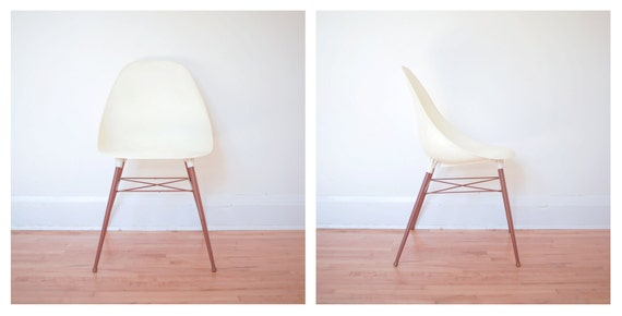 White molded plastic eames style shell chair with brown aluminum legs