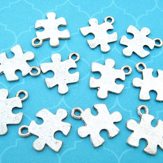 2 puzzle piece charms puzzle charms silver plated puzzle for Delicate in texture crossword clue