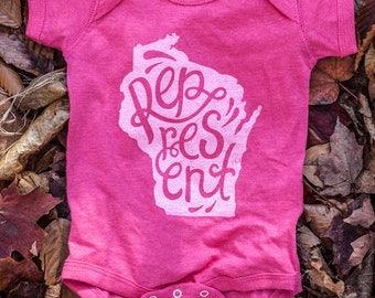 New Represent Wisconsin Pink Baby Onesie. Fuschia Baby Jumper Celebrates the Midwest. Made in the USA.