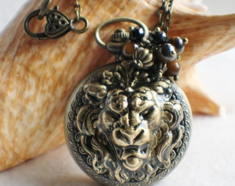 Lion watch pendant, pocket watch with lion head mounted on front cover.