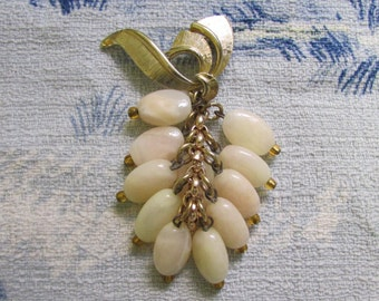 Late 1950s gold-tone ribbon swirl brooch with polished stone bunch