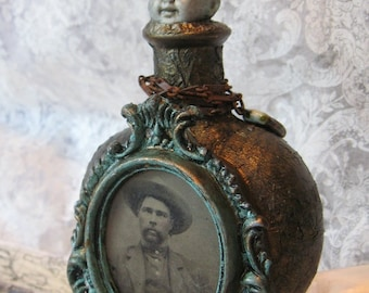 On the Shoulders of His Ancestor.  An altered art bottle with tintype, antique doll head, heavy metal crown