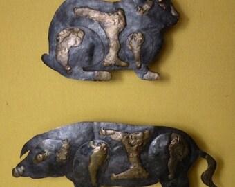 Rabbit and pig metal reliefs