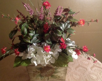 White Hydrangea with red and pink wild flowers with variegated foilage in a square container.