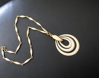 Trifari style vintage 70s gold tone metal necklace with off white enamel. Accented with dangle multi oval  shape pendant.