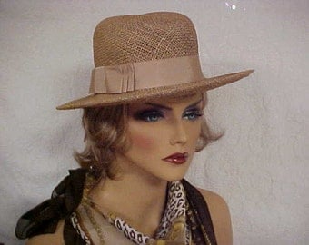 Natural straw like fedora hat with a beige grosgrain ribbon band with side bow- fits 21 1/2 inches