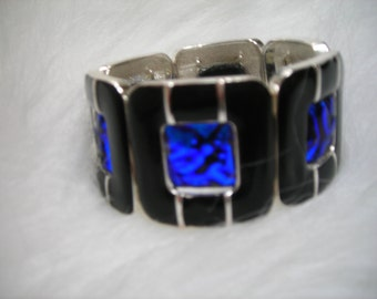 Black enameled squares with blue dichroic ripple glass inserts.  Stretches to fit