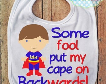 Some Fool put my cape on backwards BIB - Boy Super Hero - Baby Boy - Can choose hair color - Personalized