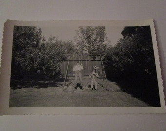 Vintage B&W Photo of two young boys on swing-set...with something in their mouths.