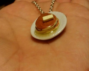 Stack of pancakes on a plate with syrup and butter necklace