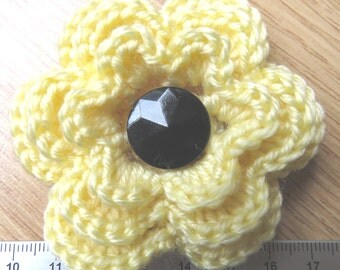 Irish crochet flower brooch in yellow wool with black glass button centre