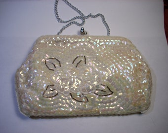A beautiful vintage white sequined purse with a beaded flower on the front