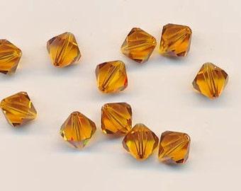 Twelve sparkling Swarovski crystals in the discontinued shape 5301: 10 mm - topaz