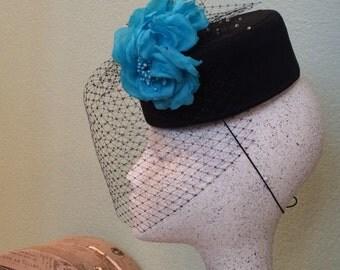 Black pillbox hat with handmade turquoise silk flowers.