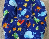 Baby Car Seat Cover is reversible with an underwater creature print on one side and a blue and white check print on the other.