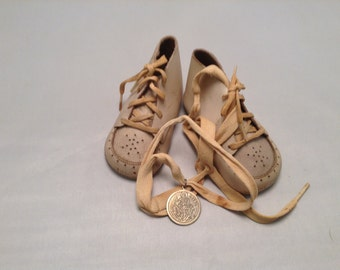 Soft baby shoes, with a holy medal pendant attached. St.Christopher medal and Virgin Mary-Pieta