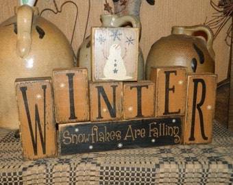 Winter snowflakes are falling primitive block sign
