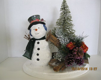 Christmas Snowman on a wood plank. Arrangements and Centerpieces