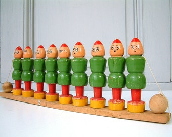 French vintage painted wood bowling skittles game with 2 balls and storage support. Green Elves. Dwarfs.