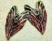 Polymer clay heart-shaped drop beads with organic patterns in shades of black, rust, and metallic golden bronze.