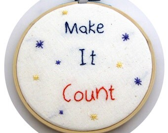 """Embroidery Hoop Wall Art Featuring """"Make It Count"""" in Blue and Ornage on 100% Off White Cotton and Decorated with Purple and Yellow Starts"""