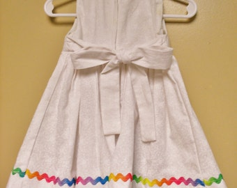 White dress sleeveless, gathers at waist, embroidery on front