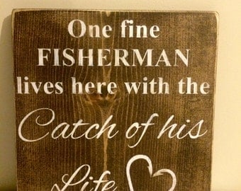 Rustic hand painted wood sign- One fine fisherman lives here with the catch of his life