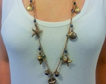Vintage gold  metal long necklace with a touch of the beach accent.
