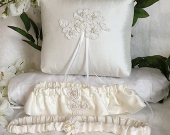 Wedding pillow, one keepsake garter and one toss garter, made with the finest duponi silk, lace cutouts with pearl insets.