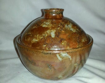 Brown casserol and lid with a golden hue.