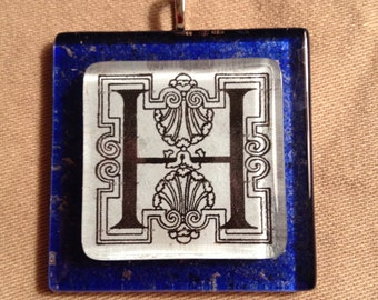 """Square glass decoupage pendant bearing the initial """"H"""" on a cobalt-blue base."""