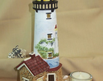 Resin lighthouse with row boat, seashells and tea light