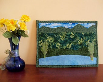 "A one-of-a-kind wall hanging of a field rimmed by mountains above and a lake below, primarily blues and greens, size 12 by 16""."