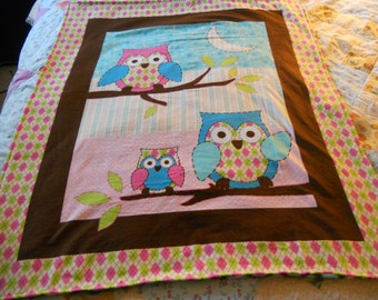 Baby blanket with three owls on a branch. really soft colors of pinks,blues and brown.