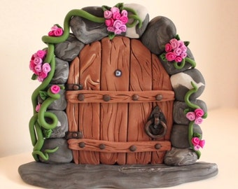 Woodland Fairy Door with Pink Flowers around a Wood Effect Door. Handmade using Polymer Clay